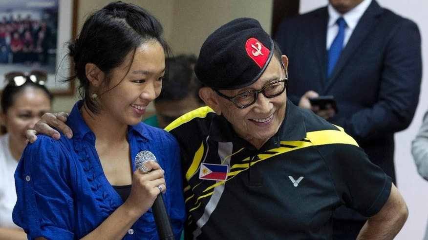 Former Philippine President Fidel Ramos puts his arm around a journalist during a press briefing at the Philippines consular office in Hong Kong, China, Tuesday, Aug. 9, 2016. Former Philippine President Fidel Ramos flew to Hong Kong on Monday for talks aimed at rekindling ties with China that have been strained by long-seething disputes in the South China Sea. (AP Photo/Ng Han Guan)