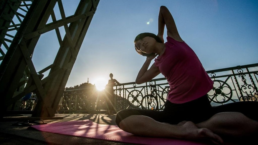 A woman participates in a group yoga exercises on Freedom Bridge in downtown Budapest, Hungary, Tuesday, August 9, 2016. Yoga instructors held classes for over 600 practitioners on Budapest's Freedom Bridge, which is closed for renovations, in an effort to popularize the discipline and practice it in a unique location. (Zoltan Balogh/MTI via AP)