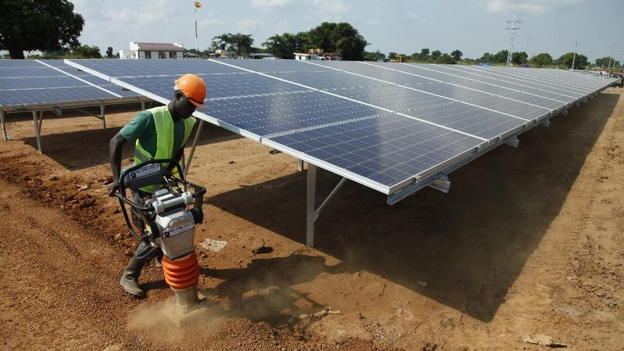 In this photo taken Thursday, June 30, 2016, a Ugandan casual worker levels the ground at a solar plant in Soroti about 300 kilometers east of Uganda capital Kampala. In this electricity-starved rural part of Uganda, men ride bicycles several kilometers (miles) to the nearest market town simply to charge their phones. That should change with the construction nearby of one of the largest solar plants in sub-Saharan Africa, where two-thirds of the population is without electricity and countries increasingly explore alternative sources of power. (AP Photo/Stephen Wandera)