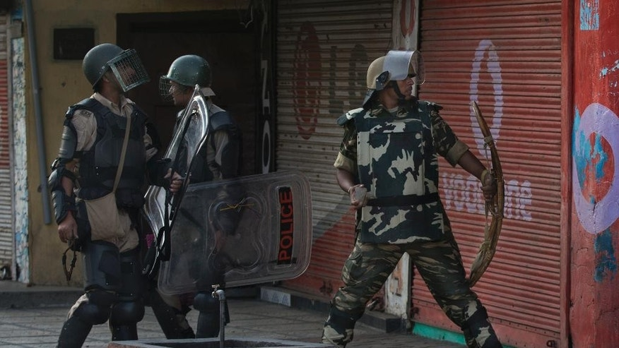 Indian paramilitary soldiers prepare to throw stones at Kashmiri Muslim protesters as they walk back towards their base camp after a day long curfew in Srinagar, Indian controlled Kashmir, Monday, Aug. 8, 2016. Kashmir has been under a security lockdown and curfew since the killing of a popular rebel commander on July 8 sparked some of the largest protests against Indian rule in recent years. (AP Photo/Dar Yasin)