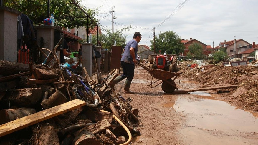 A man pushes a wheelbarrow with mud from his flooded house after a storm, in the village of Stajkovci, just east of Skopje, Macedonia, on Monday, Aug. 8, 2016. Macedonia's government declared a state of emergency Sunday in parts of the capital hit by torrential rain and floods that left at least 21 people dead, six missing and dozens injured, authorities said.(AP Photo/Boris Grdanoski)