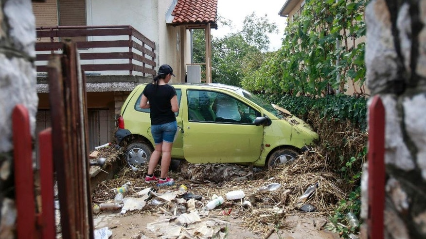 A woman stands by a damaged car in the house yard after flooding, in the village of Stajkovci, just east of Skopje, Macedonia, on Monday, Aug. 8, 2016. Macedonia's government declared a state of emergency Sunday in parts of the capital hit by torrential rain and floods that left at least 21 people dead, six missing and dozens injured, authorities said. (AP Photo/Boris Grdanoski)