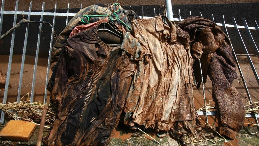 Muddy clothes, taken out of a flooded house, hang on a fence to dry after a storm, in the village of Stajkovci, just east of Skopje, Macedonia, Monday, Aug. 8, 2016. Macedonia's government declared a state of emergency Sunday in parts of the capital hit by torrential rain and floods that left at least 21 people dead, six missing and dozens injured, authorities said. (AP Photo/Boris Grdanoski)