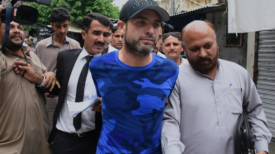 American citizen Mathew Craig Barrett, center, is escorted by officials of Federal Investigation Agency following a court appearance in Rawalpindi, Pakistan, Tuesday, Aug. 9, 2016. Pakistani authorities presented a 'blacklisted' American citizen before a judge in the city of Rawalpindi, who was arrested recently on arrival in Pakistan. Interior Ministry spokesman Sarfaraz Hussain said that Barrett was deported and blacklisted in 2011 after being found in the area of a sensitive installation. (AP Photo/Anjum Naveed)