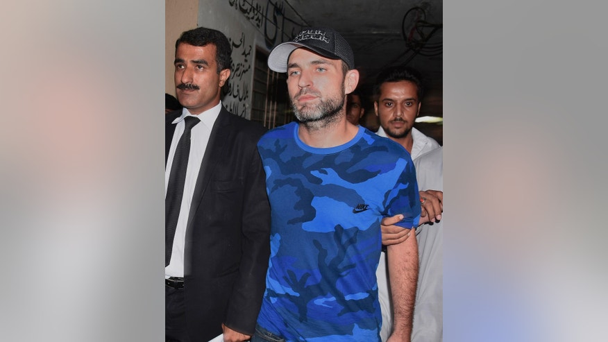 American citizen Mathew Craig Barrett, center, is escorted by officials of the Federal Investigation Agency following a court appearance in Rawalpindi, Pakistan, Tuesday, Aug. 9, 2016. Pakistani authorities presented a 'blacklisted' American citizen before a judge in the city of Rawalpindi, who was arrested recently on arrival in Pakistan. Interior Ministry spokesman Sarfaraz Hussain said that Barrett was deported and blacklisted in 2011 after being found in the area of a sensitive installation. (AP Photo/Anjum Naveed)