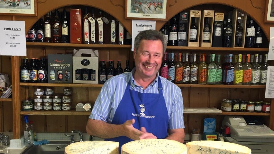 In this photo taken on Tuesday, Aug. 2, 2016, Tim Brown, the owner of the the Melton Cheeseboard, weighs out some cheese in his shop in Melton Mowbray, England. The marker of distinction for British food, the same kind that ensures Champagne can only come from the French region of the same name, is granted by the European Union and is now at risk after Britain voted to leave the 28-country bloc. The certificates, of which there are 73 across Britain for goods like Stilton cheese and Melton Mowbray pork pies, not only help farmers earn more but also shape rural communities' identities.  (AP Photo/Jonathan Shenfield)
