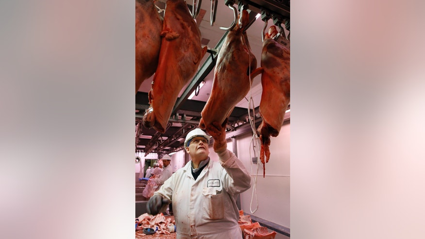 In this photo taken on Monday, July 18, 2016, a butchers hangs meat, at Rhonda Meats Ltd at Smithfield Market, in London. Welsh farmers like Rees Roberts, who have 1,000 acres with sheep, cattle and crops, can expect to earn a premium on their meats thanks to a certificate of regional authenticity. But that marker of distinction _ the same kind that ensures Champagne can only come from the French region of the same name _ is granted by the European Union and is now at risk after Britain voted to leave the 28-country bloc. (AP Photo/Kirsty Wigglesworth)