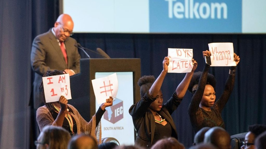 Protesters hold up papers protesting against South Africa's President Jacob Zuma, as he delivers a speech at the announcement of the results of the municipal elections in Pretoria, South Africa, Saturday, Aug. 6, 2016. South Africa's ruling party has suffered its biggest election setback since taking power at the end of apartheid a generation ago, with the African National Congress losing in the Tshwane metropolitan area that includes the country's capital, Pretoria. But it held a slight lead Saturday in the country's biggest city, Johannesburg, with 99 percent of votes counted. (AP Photo/Herman Verwey)