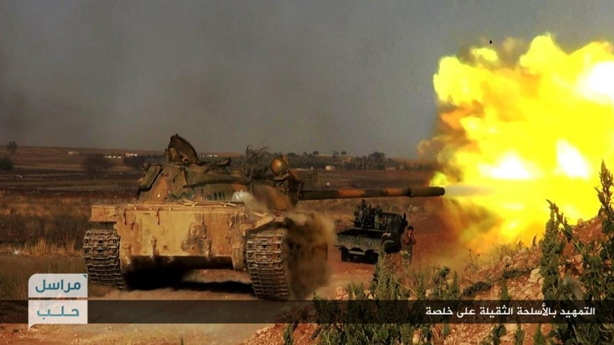 """FILE - This file image posted on the Twitter page of Syria's al-Qaida-linked Nusra Front on Tuesday June 14, 2016, which is consistent with AP reporting, shows a Nusra Front tank firing at Syrian troops and pro-government gunmen at the hilltop of Khalsa village, southern Aleppo, Syria. Arabic, bottom right, reads, """"heavy shelling ahead of advances on Khalsa."""" Within minutes of news breaking of a coup against Recep Tayyeb Erdogan, government-held areas in Syria broke out in celebratory gunfire that lasted throughout the night. In bars across the capital Damascus, revelers celebrated the news, drinking to the removal of Turkey's strongman they blame for fueling their country's five-year civil war. But Erdogan survived, and judging by the surprise reversal of rebel fortunes in Aleppo this week, so has his support for the rebels. (Al-Nusra Front Twitter page via AP, File)"""