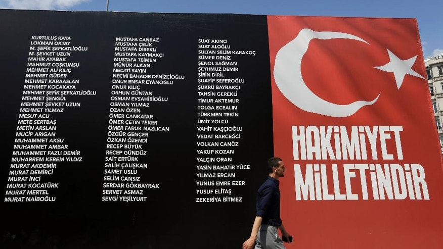 A pedestrian passes a sign commemorating people who died fighting the July 15th coup, as the banner with the Turkish flag reads ''Sovereignty belongs to the people'' at Taksim Square in Istanbul, Monday, Aug. 8, 2016. Turkey will continue fighting whatever powers seek to undermine the government, President Recep Tayyip Erdogan vowed Sunday as he addressed a massive flag-waving rally in Istanbul in the wake of the country's abortive July 15 coup. (AP Photo/Thanassis Stavrakis)