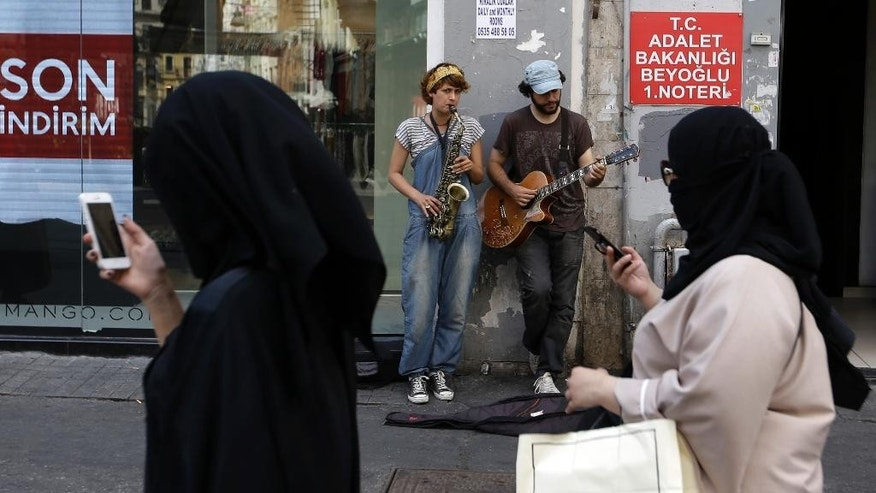Tourists check their cellphones as street artists play music in Istanbul, Tuesday, Aug. 9, 2016.  Life has returned to normal, although a welling up of national pride and broad support for actions against the perpetrators of the failed July 15 military coup attempt, has drawn daily street demonstrations in support of the government.  (AP Photo/Thanassis Stavrakis)