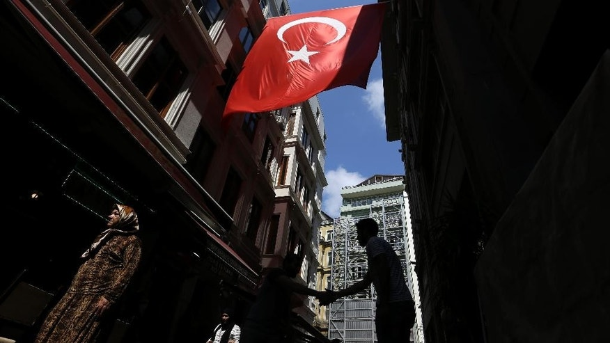 Pedestrians pass under a Turkish flag as two men shake hands in Istanbul, Tuesday, Aug. 9, 2016. A welling up of national pride and broad support for actions against the perpetrators of the failed July 15 military coup attempt, has drawn daily street demonstrations in support of the government and popular use of national emblems. (AP Photo/Thanassis Stavrakis)