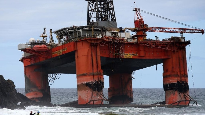 People observe the Transocean Winner drilling rig off the coast of the Isle of Lewis, Scotland, after it ran aground in severe weather conditions, Tuesday Aug. 9, 2016.  The oil rig, carrying 280 tonnes of diesel, broke free of its tug and ran aground on the remote Scottish island where it is being monitored by a counter-pollution team.  (Andrew Milligan / PA via AP)