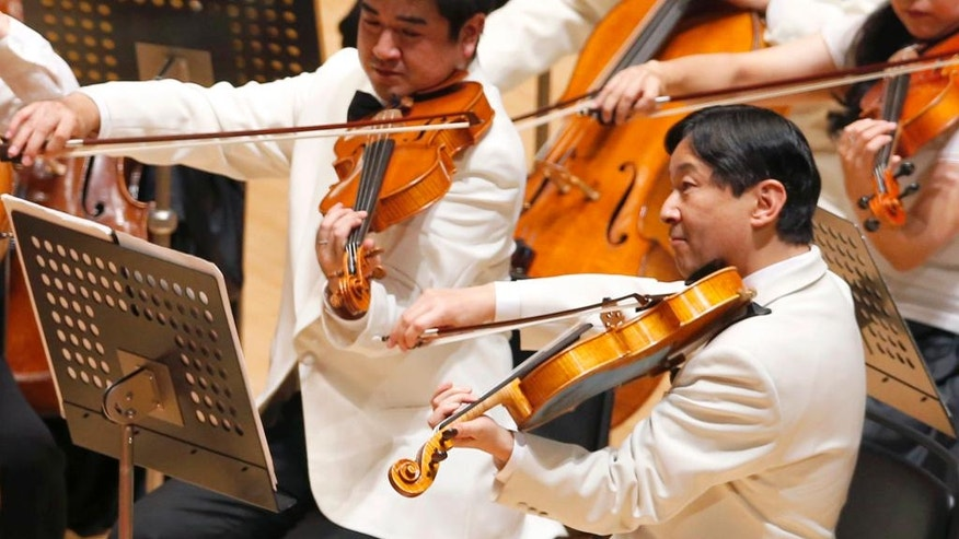 FILE - In this  July 7, 2013, file photo, Japan's Crown Prince Naruhito, right, plays the viola during a concert of the Gakushuin university's alumni in Tokyo. Emperor Akihito's video message on Monday, Aug. 8, 2016, though subtle, conveyed his wish to abdicate, and the attention now goes to his elder son Naruhito, the first in line to Japan's Chrysanthemum throne. Naruhito would be the 126th emperor in a line believed to date to the fifth century. (AP Photo/Shizuo Kambayashi, Pool, File)