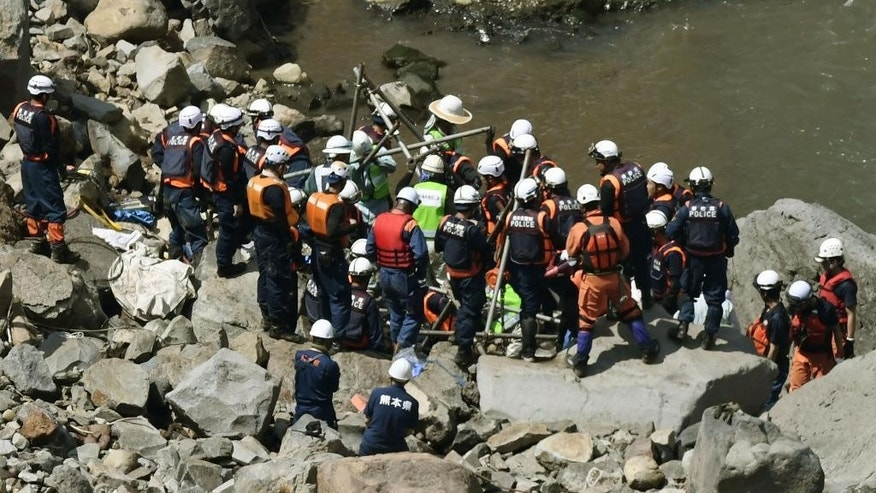 Police officers and firefighters work to retrieve a wrecked car that may hold the final victim of two deadly earthquakes that hit southern Japan nearly four month ago from a riverbank in Minamiaso, Kumamoto, southern Japan, Wednesday, Aug. 10, 2016. Japanese media say the vehicle is buried in sand and rocks down river from a bridge that collapsed into a deep gully after the second earthquake. Hikaru Yamato, a 22-year-old student, was driving home when the magnitude 7.3 earthquake struck on April 16. (Sadayuki Goto/Kyodo News via AP)