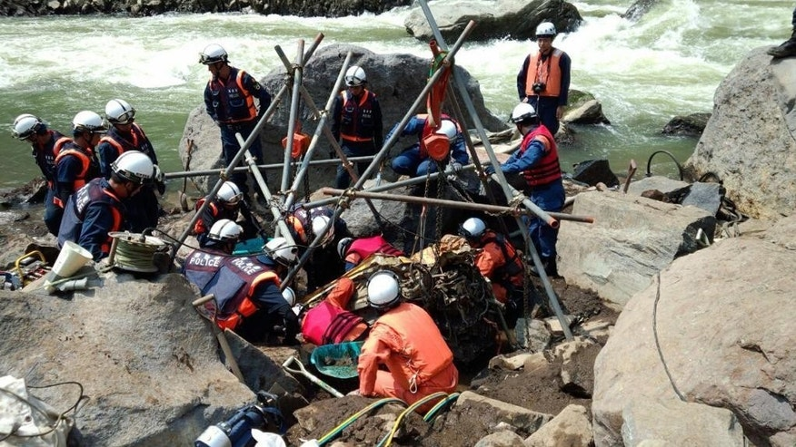 In this photo released by Kumamoto Prefecture Government, police officers and firefighters work to retrieve a wrecked car that may hold the final victim of two deadly earthquakes that hit southern Japan nearly four month ago from a riverbank in Minamiaso, Kumamoto, southern Japan, Wednesday, Aug. 10, 2016. Japanese media say the vehicle is buried in sand and rocks down river from a bridge that collapsed into a deep gully after the second earthquake. Hikaru Yamato, a 22-year-old student, was driving home when the magnitude 7.3 earthquake struck on April 16. (Kumamoto Prefecture Government via AP)
