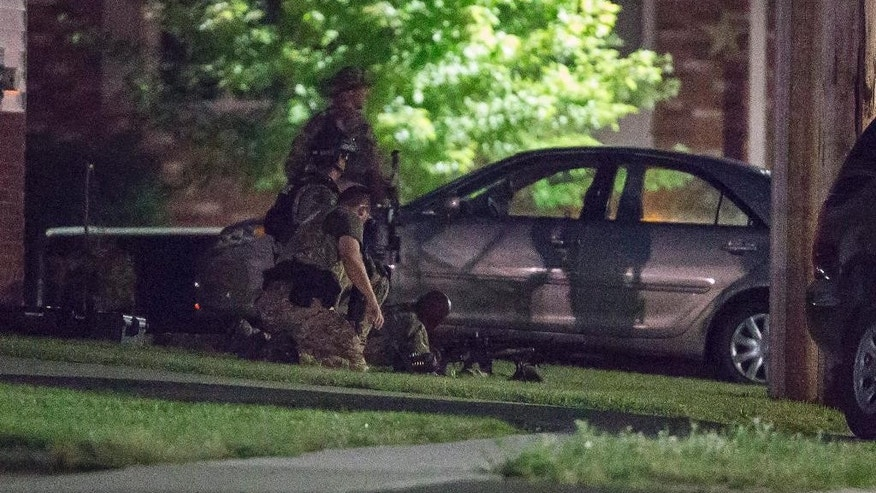 Police keep watch around a house in Strathroy, Ontario, Wednesday, Aug. 10, 2016. Canada's national police force says it has halted a possible terrorist threat, but it is providing few other details. (Geoff Robins/The Canadian Press via AP)