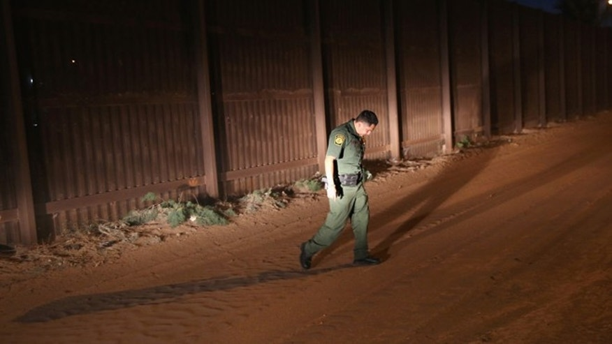 CALEXICO, CA - NOVEMBER 15:  A U.S. Border Patrol agent looks for tracks along the U.S.-Mexico border fence on November 15, 2013 in Calexico, California. The fence separates the large Mexican city of Mexicali with Calexico, CA, and is a frequent illegal crossing point for immigrant smugglers. (Photo by John Moore/Getty Images)
