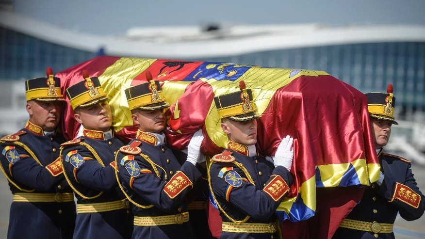 An honor guard soldiers carry the flag-draped coffin of Anne of Romania, wife of Romania's last monarch King Michael, before a religious service, in Otopeni, Romania, Tuesday, Aug. 9, 2016. The body of Anne of Romania, the wife of the country's ex-king, arrived in Bucharest Tuesday for the biggest royal funeral in almost 80 years. (AP Photo/Andreea Alexandru)