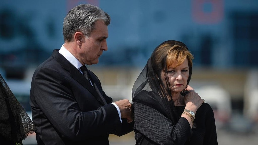 Princess Margaret, right, daughter of Romania's last monarch King Michael, stands as her husband Prince Radu of Romania adjusts her scarf, before a religious service as the body of Anne of Romania arrives in Otopeni, Romania, Tuesday, Aug. 9, 2016. The body of Anne of Romania, the wife of the country's ex-king, arrived in Bucharest Tuesday for the biggest royal funeral in almost 80 years. (AP Photo/Andreea Alexandru)