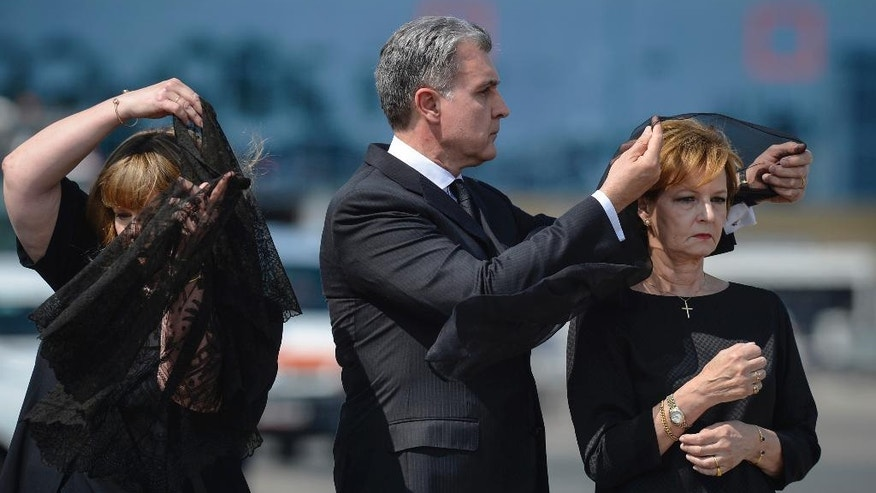 Princess Margaret, right, daughter of Romania's last monarch King Michael, stands as her husband Prince Radu of Romania, center, adjusts her scarf, before a religious service as the body of Anne of Romania arrives in Otopeni, Romania, Tuesday, Aug. 9, 2016. The body of Anne of Romania, the wife of the country's ex-king, arrived in Bucharest Tuesday for the biggest royal funeral in almost 80 years. (AP Photo/Andreea Alexandru)