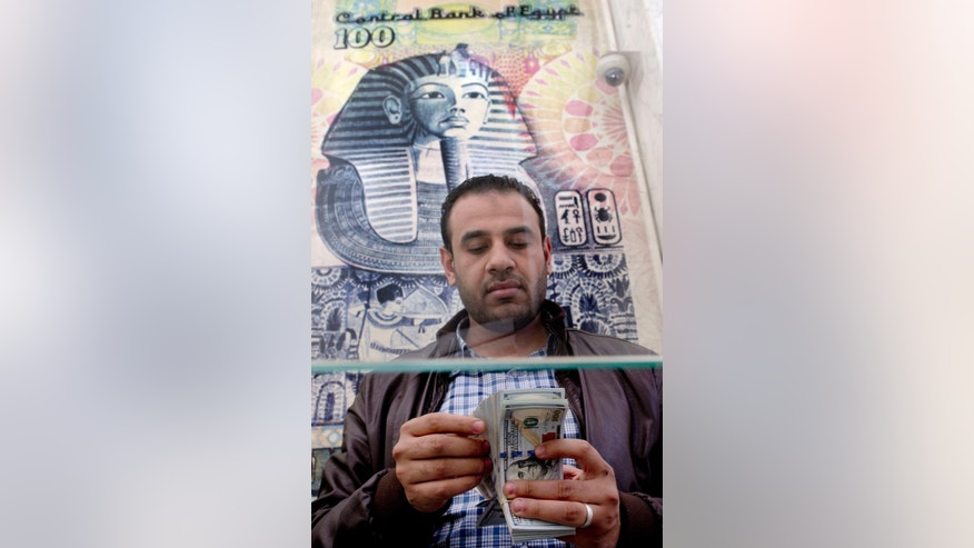 """FILE -- In this March 14, 2016 file photo, a man counts U.S dollars at an exchange office in Cairo, Egypt. Al-Ahram, Egypt's flagship state newspaper, quoted Ali Abdel-Al, the country's parliament speaker, in its Wednesday, Aug. 10, 2016 edition, as saying he wished new legislation toughening punishments for illegal foreign currency trading would include the death penalty. The newspaper quoted Abdel-Al as saying that Egypt is subjected to an """"economic war"""" and a """"conspiracy"""" that must be confronted. Abdel-Al, has also called for the closure across the country of all foreign exchange bureaus -- which are accused of pushing down the value of the Egyptian pound, describing them as a """"cancer"""" in the nation's economy. (AP Photo/Amr Nabil, File)"""