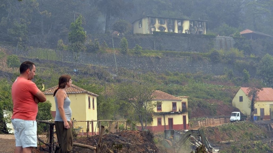 A couple looks at the damaged buildings of their farm in the outskirts of Funchal, the capital of Portugal's Madeira island Wednesday, Aug. 10 2016. The farm was caught in the forest fires that are raging in Madeira and have forced the evacuation of more than 1,000 residents and tourists. (AP Photo/Helder Santos)