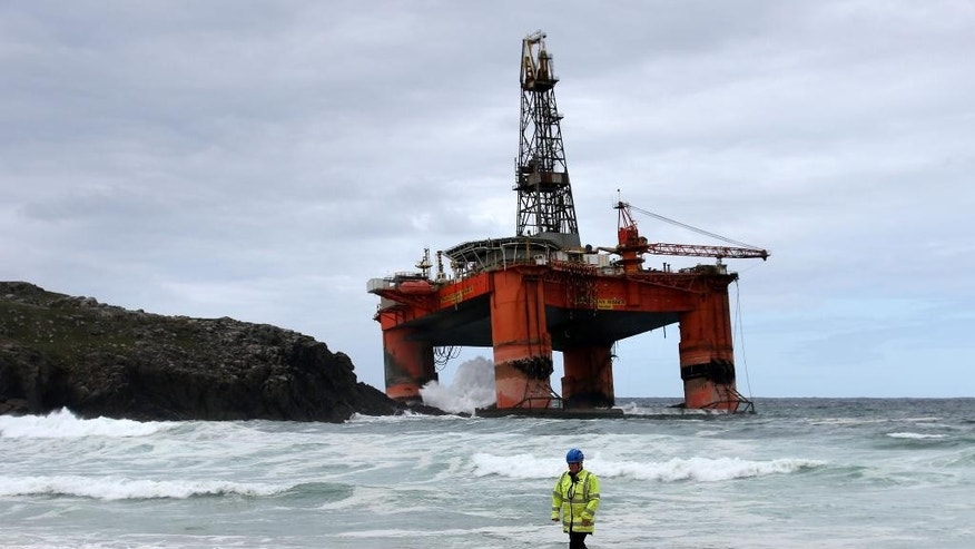 A coastguard official monitors the shoreline with Transocean Winner drilling rig off the coast of the Isle of Lewis, Scotland, after it ran aground in severe weather conditions, Tuesday Aug. 9, 2016.  The oil rig, carrying 280 tonnes of diesel, broke free of its tug and ran aground on the remote Scottish island where it is being monitored by a counter-pollution team.  (Andrew Milligan / PA via AP)
