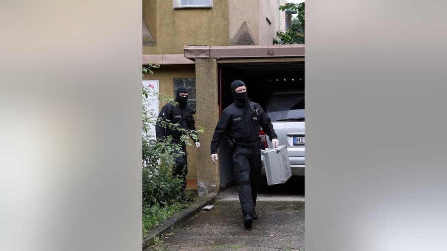 Police leave a house in Hildesheim, Germany after a raid Wednesday Aug, 10, 2016. German prosecutors say they've carried out searches linked to three suspected supporters of the Islamic State group. The federal prosecutor's office said that three targeted in Wednesday's raids are suspected of seeking members and supporters for IS since last year, news agency dpa reported. The regional WAZ newspaper reported that the searches took place at premises in Duisburg and Dortmund in western Germany and in Hildesheim in northern Germany. (Christian Gossmann/dpa via AP)