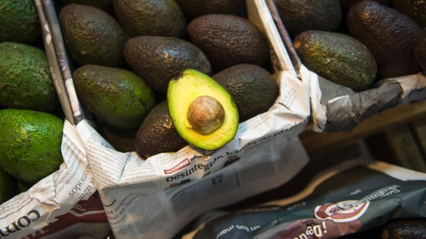 Avocados are displayed for sale in a large market in Mexico City, Tuesday, Aug. 9, 2016. Avocado trees flourish at about the same altitude and climate as the pine and fir forests of Michoacan, the state that produces most of Mexico's avocados. That has led farmers to fight a game of cat-and-mouse with authorities, thinning the forests and planting young avocado trees under the canopy. (AP Photo/Nick Wagner)