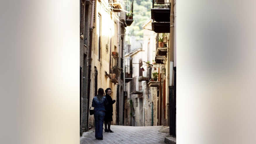 "FILE -- In this file photo taken on April 24, 2006, women walk in Corleone, Italy. Premier Matteo Renzi's Cabinet dissolved Corleone's municipal government because  of Mafia infiltrations and put its City Hall under temporary control of the interior ministry. Corleone is the Sicilian town inspiring the fictional crime clan's name in ""The Godfather"" novel and movie. (AP Photo/Gregorio Borgia)"