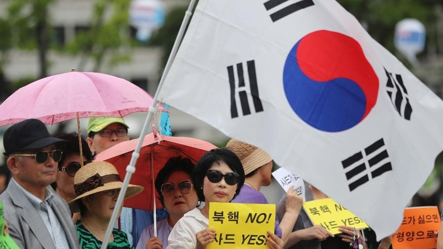 "FILE - In this Monday, July 18, 2016 file photo, South Koreans hold signs and a national flag during a rally to support a plan to deploy an advanced U.S. missile defense system called Terminal High-Altitude Area Defense, or THAAD, in Seoul, South Korea. China's simmering feud with South Korea over the deployment of an American missile defense system is just the latest in a string of foreign policy challenges piling up on President Xi Jinping's desk as he prepares to host the annual summit of the G20 nations in September. The signs read ""No, North Korea's Nuclear and Yes, THAAD."" (AP Photo/Lee Jin-man, File)"