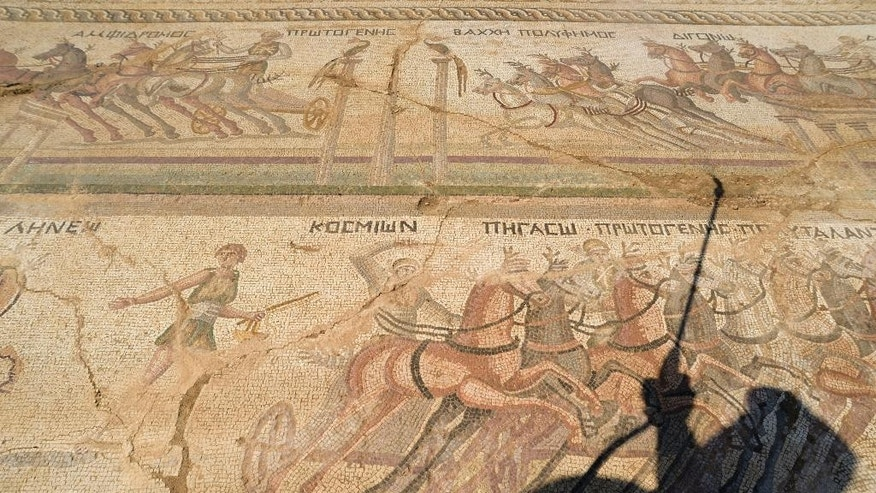 The shadow of Archeologist Fryni Hadjichristofi is cast over a rare mosaic floor dating to the 4th century depicting scenes from a chariot race in the hippodrome, uncovered and shown to the media for the first time Wednesday Aug. 10, 2016, in Akaki village outside from capital Nicosia, Cyprus.  The extraordinary mosaic floor is 11 meters long and four meters wide (36 by 13 feet) depicting scenes of a chariot race in the hippodrome in ancient Rome, in ornate detail.  (AP Photo/Pavlos Vrionides)