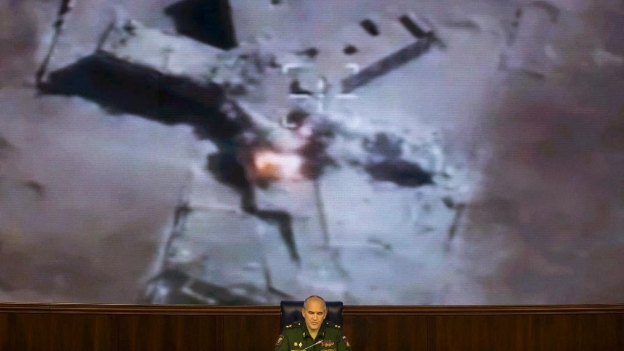 Lt.-Gen. Sergei Rudskoi of the Russian Military General Staff speaks to the media, as a video released by the Russian Defense Ministry shows a target hit in an air strike on screen, at a Russian Defense Ministry building in Moscow, Russia, Wednesday, Aug. 10, 2016. Rudskoi said that fighting in Aleppo will cease for three hours daily to allow humanitarian aid deliveries. (AP Photo/Ivan Sekretarev)