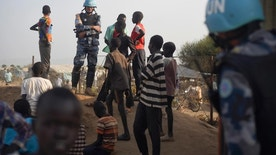 """FILE---In this file photo taken Tuesday, Jan. 19, 2016, a United Nations peacekeeper stands with displaced children on a wall around the United Nations base in the capital Juba, South Sudan. South Sudan on Wednesday, Aug. 10, 2016, rejected a U.S. proposal for the U.N. Security Council to send 4,000 additional troops to the East African country to restore calm, saying it """"seriously undermines"""" its sovereignty and threatens a return to colonialism. (AP Photo/Jason Patinkin/File)"""