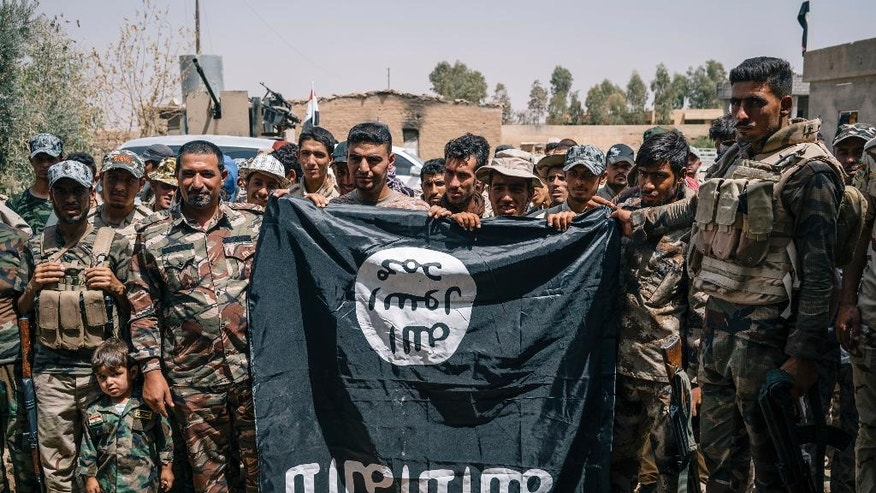Sheikh Nozhan Selman, second from the right, poses for a picture with his men holding an Islamic State flag they captured in Hajj Ali, Iraq, Tuesday, August 9, 2016. Sheikh Nazhan Sakhar and the 700 men under his command are among the forces preparing to retake the Iraqi city of Mosul from the Islamic state group. He says his Sunni militia is critical to defeating IS and maintaining peace afterward because his fighters, unlike the majority of Iraq's military, are local to Mosul. (AP Photo/Alice Martins)