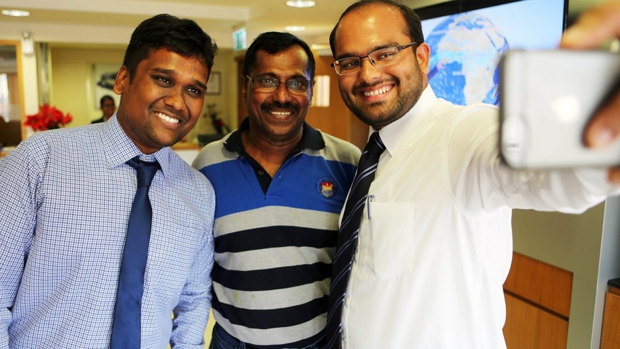 Aug. 10, 2016: Mohamed Basheer, center, a fleet sales coordinator at Al Tayer Motors, takes a selfie with bankers eager for his business in Dubai, United Arab Emirates. Basheer survived the Aug. 3 crash-landing of an Emirates airliner in Dubai and won $1 million in a sweepstakes drawing by Dubai Duty Free the following Tuesday.