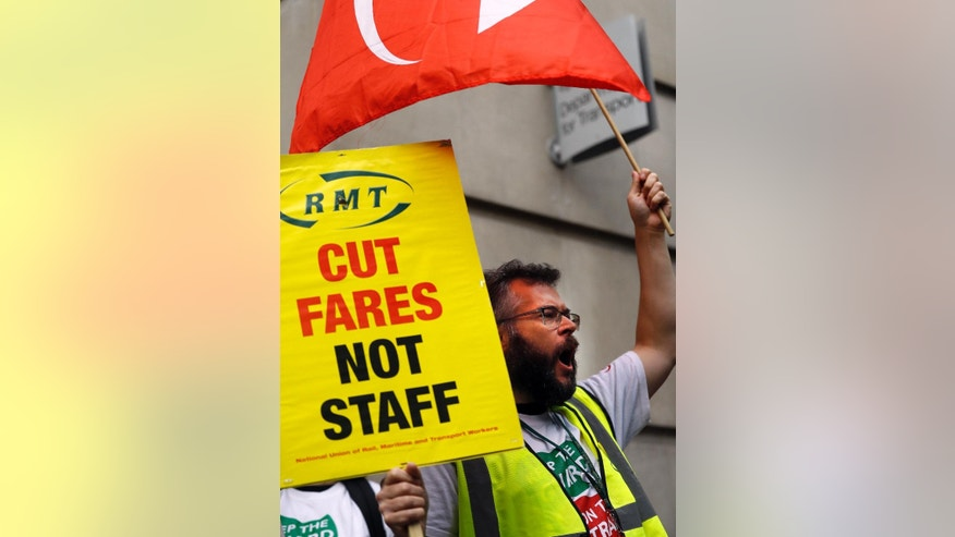 A protester displays a placard and waves a banner outside the Transport Department in London, Wednesday, Aug. 10, 2016. Rail workers staged a protest over the Southern Rail dispute followed at 5.30pm by a march from Victoria Station by commuters and the Campaign for Better Transport. (AP Photo/Frank Augstein)