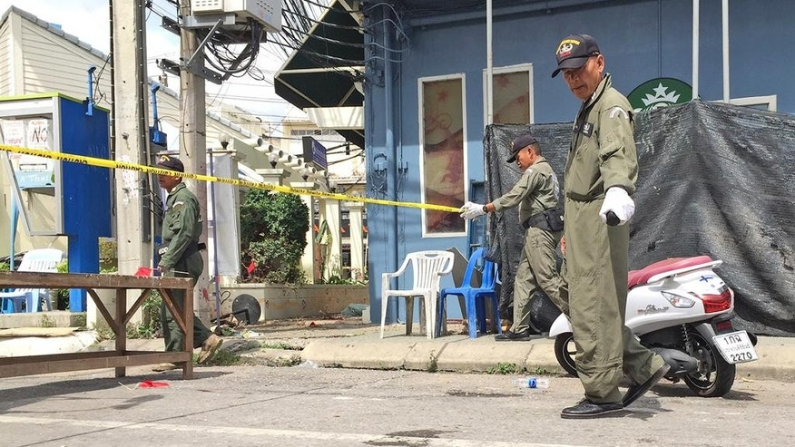Investigators work at the scene of an explosion in the resort town of Hua Hin, 240 kilometers (150 miles) south of Bangkok, Thailand Friday, Aug. 12, 2016. The blast followed a series of two explosions in Hua Hin Thursday evening that left one person dead and a number injured. (AP Photo/Jerry Harmer)