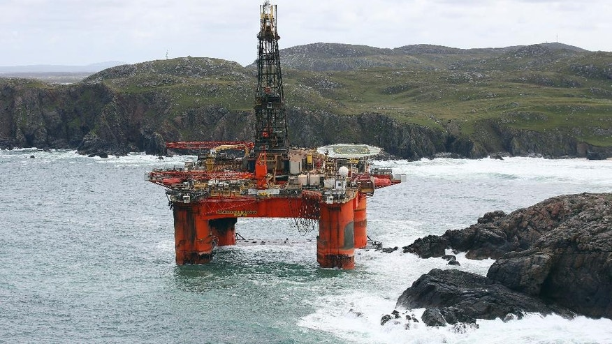 The Transocean Winner drilling rig is seen off the coast of the Isle of Lewis, Scotland, after it ran aground in severe weather conditions, Tuesday Aug. 9, 2016.  The oil rig, carrying 280 tonnes of diesel, broke free of its tug and ran aground on the remote Scottish beach where it is being monitored by a counter-pollution team.  (Andrew Milligan / PA via AP)