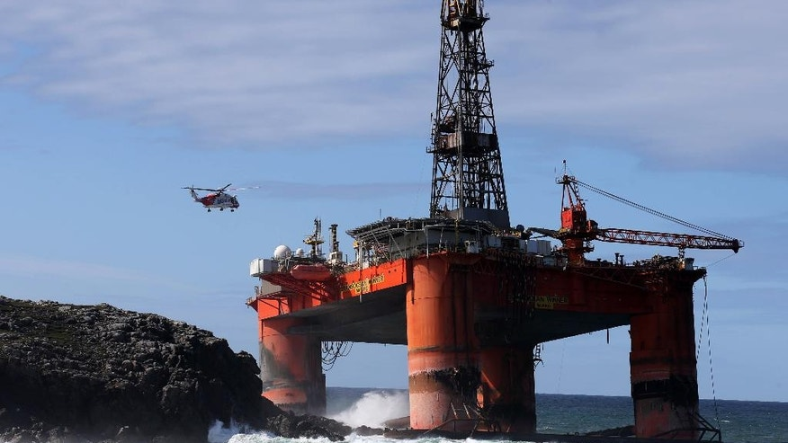 A coastguard helicopter prepares to winch a salvage expert aboard the Transocean Winner drilling rig off the coast of the Isle of Lewis, Scotland, after it ran aground in severe weather conditions, Tuesday Aug. 9, 2016.  The oil rig, carrying 280 tonnes of diesel, broke free of its tug and ran aground on the remote Scottish island where it is being monitored by a counter-pollution team.  (Andrew Milligan / PA via AP)
