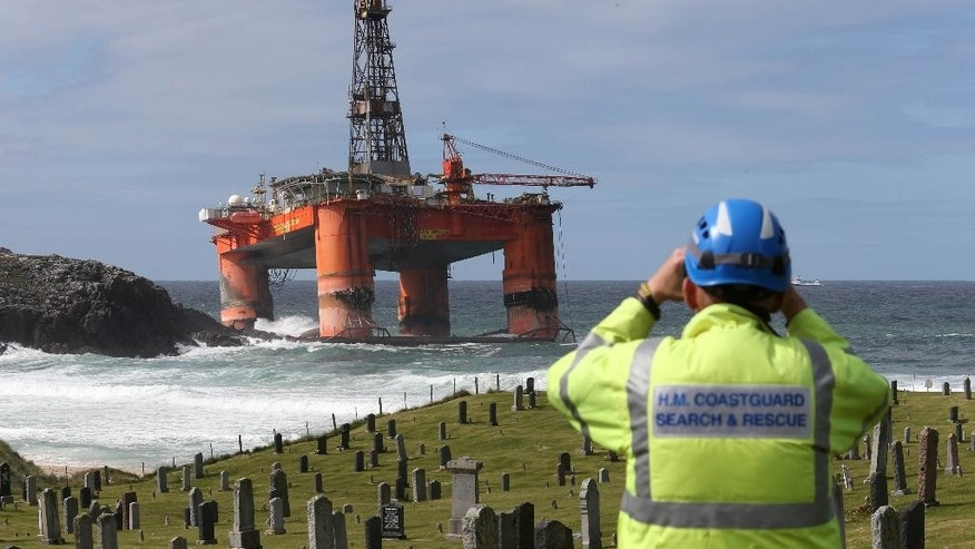 A coastguard official monitors the Transocean Winner drilling rig off the coast of the Isle of Lewis, Scotland, after it ran aground in severe weather conditions, Tuesday Aug. 9, 2016.  The oil rig, carrying 280 tonnes of diesel, broke free of its tug and ran aground on the remote Scottish island where it is being monitored by a counter-pollution team.  (Andrew Milligan / PA via AP)