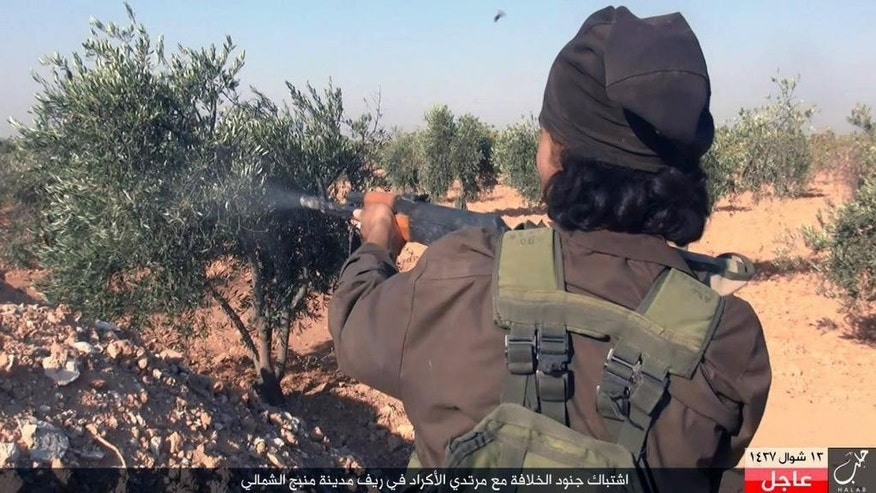 "This image posted online on Monday, July. 18, 2016, by supporters of the Islamic State militant group on an anonymous photo sharing website, shows an Islamic State fighter fires his weapon during clashes with the Kurdish-led Syria Democratic Forces in Manbij, in Aleppo province, Syria. The Arabic caption on the photo reads, ""Soldiers of the caliphate clash with Kurdish infidels in northern countryside of Manbij."" (militant photo via AP)"