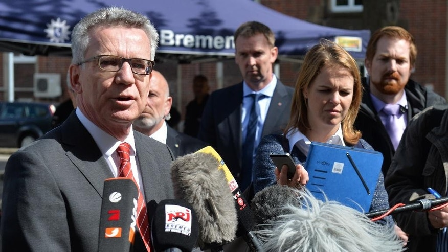 German Interior Minister Thomas de Maiziere, left, speaks to the media during his visit to Bremen, northern Germany, Wednesday, Aug. 10, 2016. ( Carmen Jaspersen/dpa via AP)