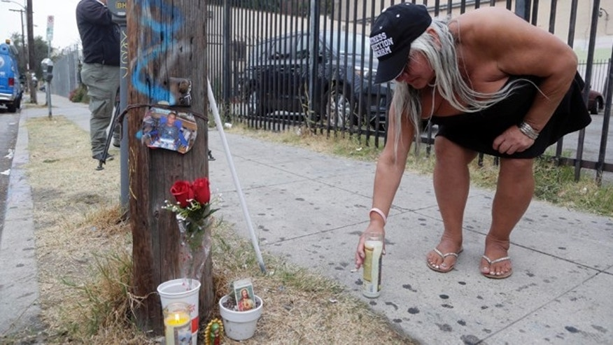 Maria Ramirez places a candle near a police involved shooting of a teen in Los Angeles on Wednesday, Aug. 10, 2016.