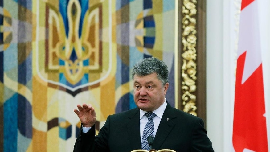 FILE - In this file photo dated Monday, July 11, 2016, Ukrainian President Petro Poroshenko gestures during a news conference in Kiev, Ukraine.  In a statement Thursday Aug. 11, 2016, Ukrainian President Poroshenko says he has ordered the army to be put on combat alert on the de-facto border with Crimea and the line of contact in eastern Ukraine, in response to relations with Russia.  (AP Photo/Efrem Lukatsky, FILE)