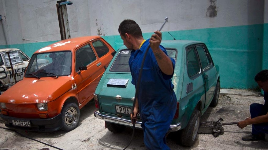 Ramses Fernandez works on a Fiat Polski 126p in Havana, Cuba, Tuesday, August 10, 2016. Fernandez owns a Polski that is his most cherished possession. It is barely larger than a refrigerator, with the legroom of an economy airplane seat and a little more horsepower than a riding lawnmower. (AP Photo/Ramon Espinosa)