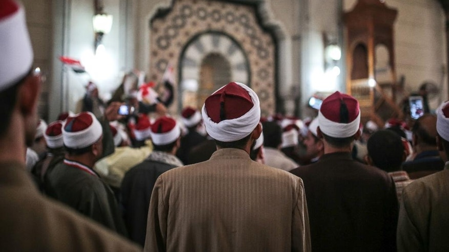 FILE - In this Feb. 3, 2015 file photo, Egyptian clerics from Al-Azhar institution rally to denounce terrorism and show solidarity with the Egyptian government and security forces at a mosque in central, Cairo, Egypt. In July 2016 the Egyptian government launched a radical bid to establish control over Egypt's religious discourse, mandating that all imams at all mosques across the country read pre-written sermons distributed by the ministry. The government describes the initiative, unprecedented in Egypt's history, as a means of weeding out extremist ideology, but it has proved extremely unpopular, with critics accusing the state of stifling the freedom of thought and creativity of the clerics. (AP Photo/Mosa'ab Elshamy, File)