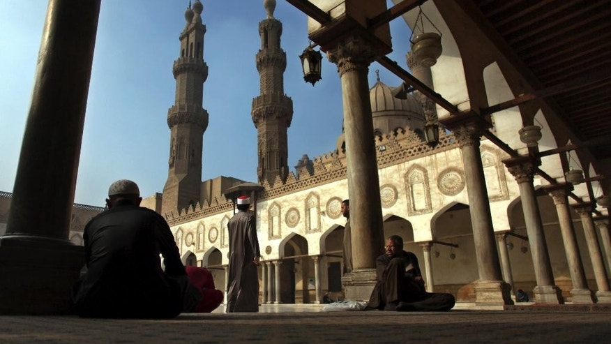 FILE - In this Dec. 28, 2012 file photo, Muslim men wait for the Friday noon prayer at Al-Azhar Mosque in Cairo, Egypt. In July 2016 the Egyptian government launched a radical bid to establish control over Egypt's religious discourse, mandating that all imams at all mosques across the country read pre-written sermons distributed by the ministry. The government describes the initiative, unprecedented in Egypt's history, as a means of weeding out extremist ideology, but it has proved extremely unpopular, with critics accusing the state of stifling the freedom of thought and creativity of the clerics. (AP Photo/Khalil Hamra, File)
