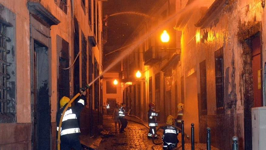 In this photo taken late Tuesday, Aug. 9 2016, firefighters battle a fire that reached the old center of Funchal, the capital of Portugal's Madeira island. Forest fires in Madeira forced the evacuation of more than 1,000 residents and tourists. (AP Photo/Helder Santos)